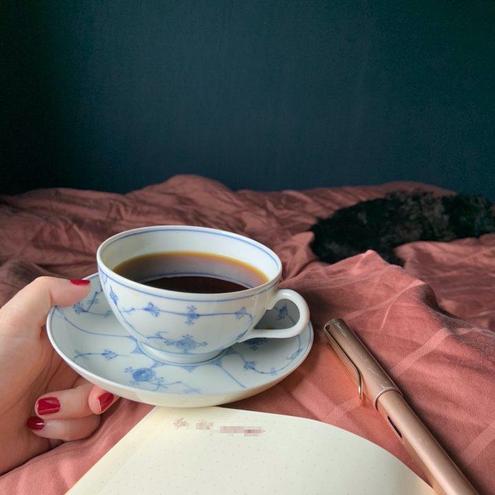 Notatbok, penn og kaffe på senga