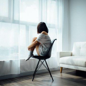 person som sitter alene på en stol forran et vindu