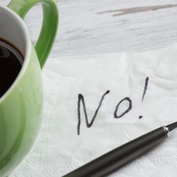 """teksten """"no"""" på en serviett ved siden av en kaffekopp"""